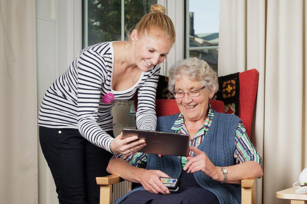 Illustrasjonsfoto. Ung dame viser en eldre dame et nettbrett