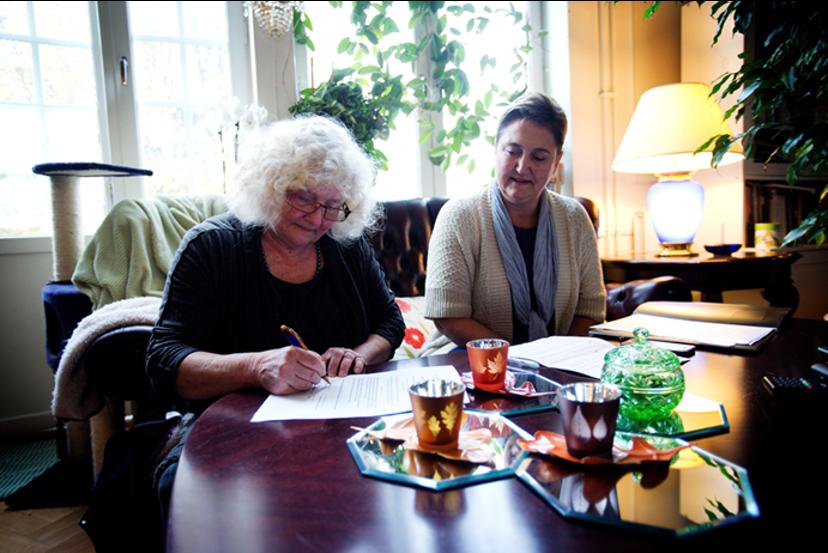 Illsutrasjon. To damer sitter ved stuebordet, en skriver på et ark, den andre ser på.